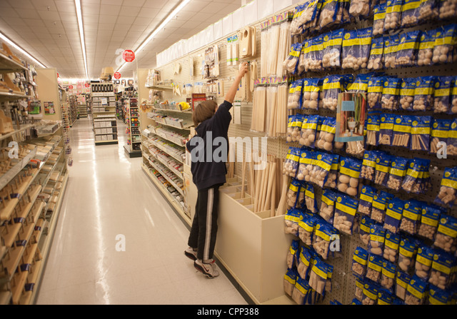 Nine year old boy trying to reach art supplies in a craft store, United States. - Stock Image