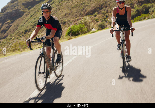Two athletes going down the hill on racing bicycles. Man and woman cyclist riding down the country road. Triathlon - Stock Image