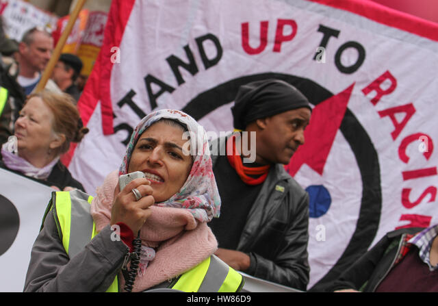 London, UK. March 18, 2017: A demonstrator speaks through a mega phone ahed of the Stand Up To Racism demonstration - Stock Image