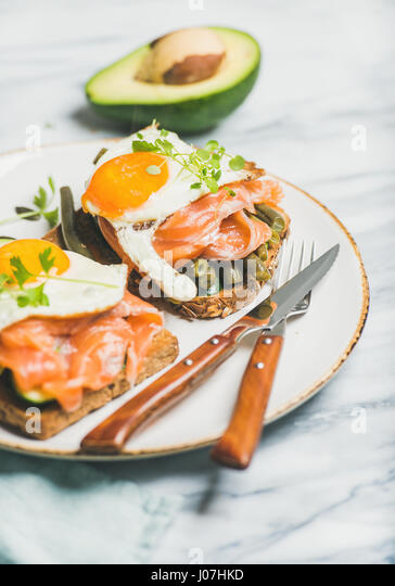 Salmon, avocado, fried egg, sauted green beans and sprouts sandwiches - Stock Image