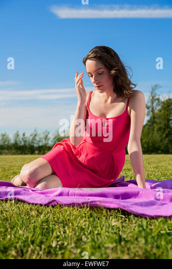 Young shy woman on the purple blanket - Stock Image