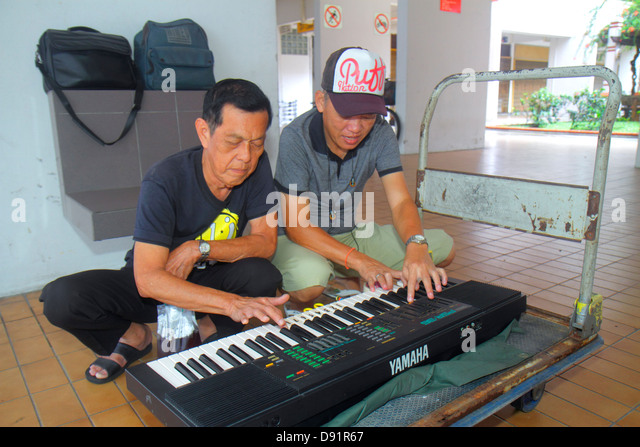 Singapore Jalan Besar Asian man playing electric keyboard Yamaha duet music hobby - Stock Image