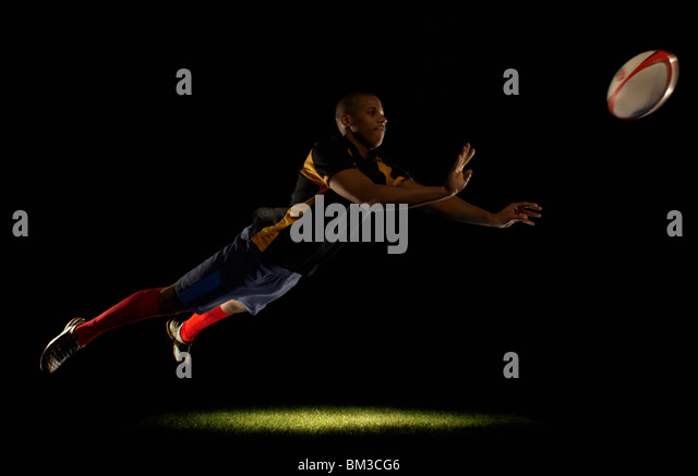 Rugby player diving whilst passing ball - Stock Image
