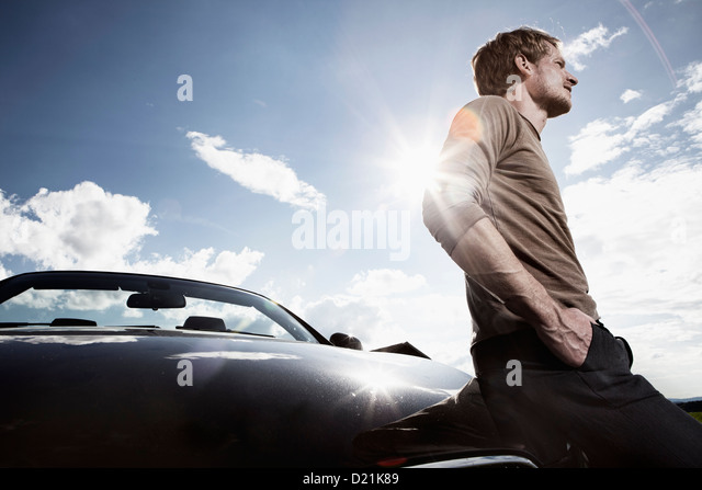 Germany, Bavaria, Mid adult man standing by car - Stock Image