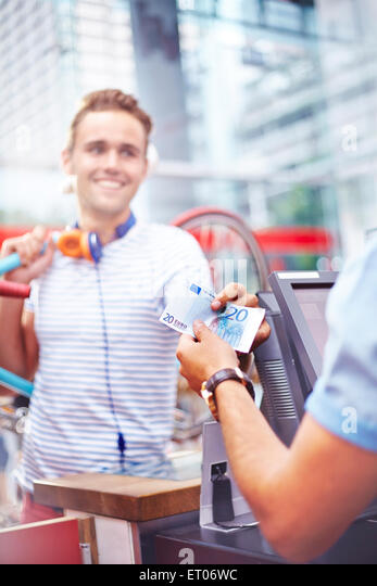 Customer paying worker in cafe with twenty Euro banknote - Stock Image