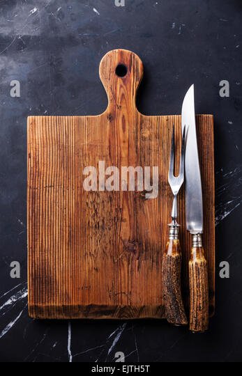 Chopping cutting board and fork and knife carving set on dark marble background - Stock Image