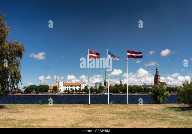 Panorama of Riga against the blue sky with clouds and the national flags of Latvia and Riga - Stock Image