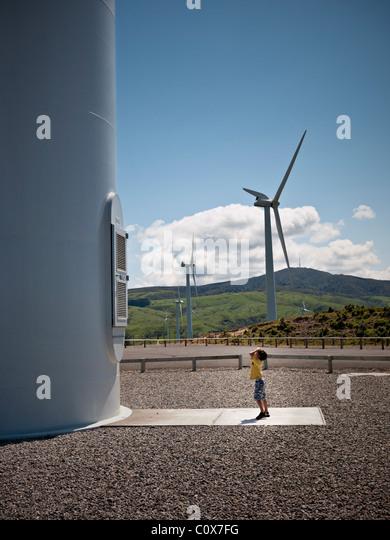 Boy looks up at wind turbine, Te Apiti wind farm, New Zealand. - Stock Image