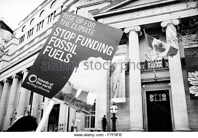 A placard protesting against fossil fuel funding is carried past the Canadian High Commission. - Stock Image
