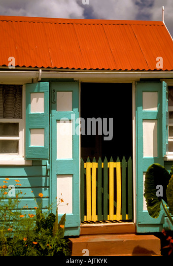 Island of Nevis St Kitts and Nevis Caribbean island, colorful traditional home red green white building architecture - Stock Image