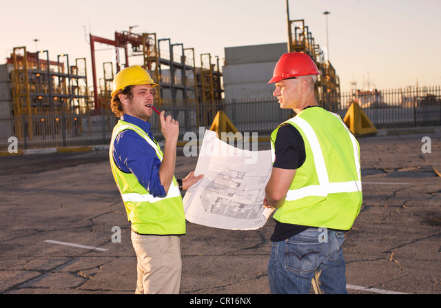 Construction workers reading blueprint - Stock Image