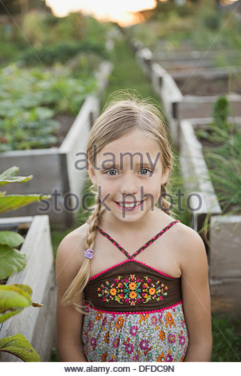 Portrait of cute girl standing in community garden - Stock-Bilder