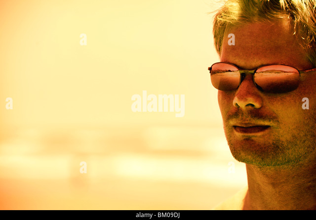 Young man wearing sunglasses at sunset by the ocean - Stock Image