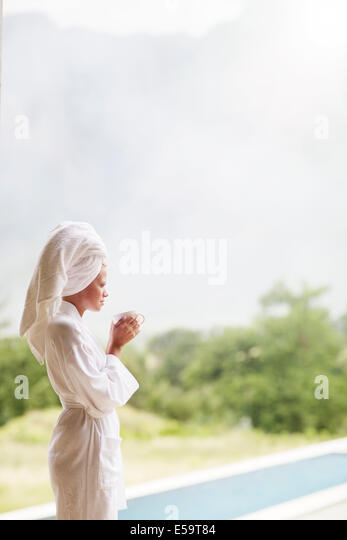 Woman in bathrobe drinking coffee outdoors - Stock Image