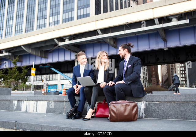 Business people discussing while using laptop against building - Stock-Bilder