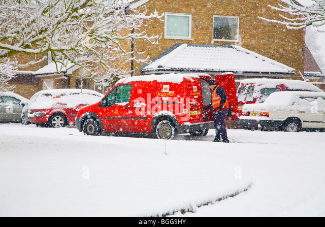 Postman delivering mail during a heavy snowstorm - Stock Image