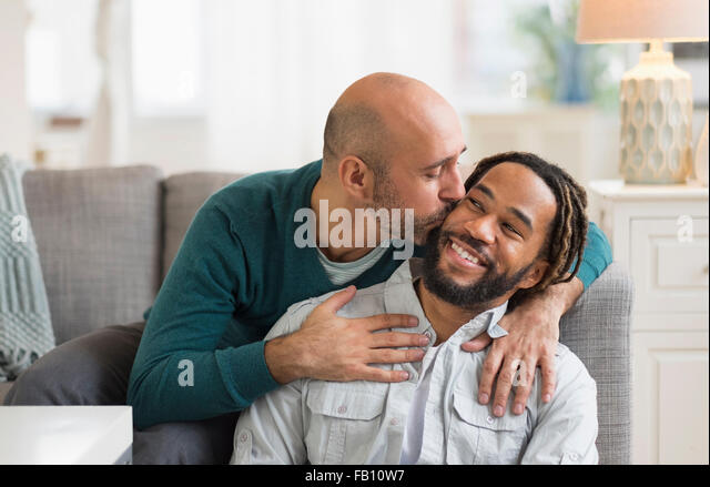 Homosexual couple kissing by sofa in living room - Stock Image