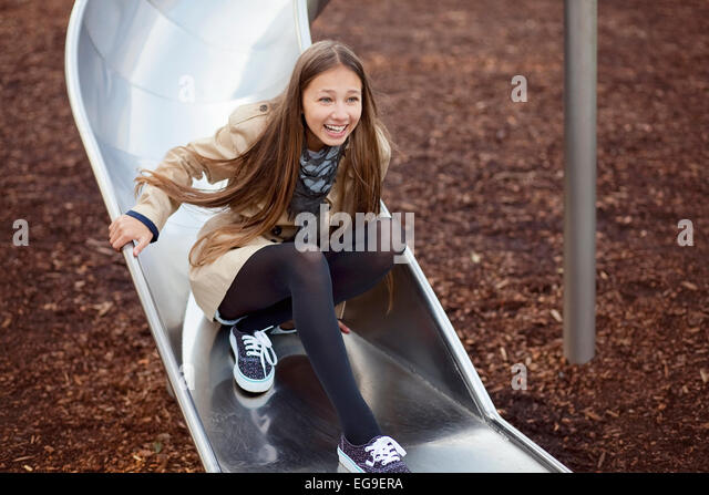 Young girl (12-13) having fun on slide - Stock Image