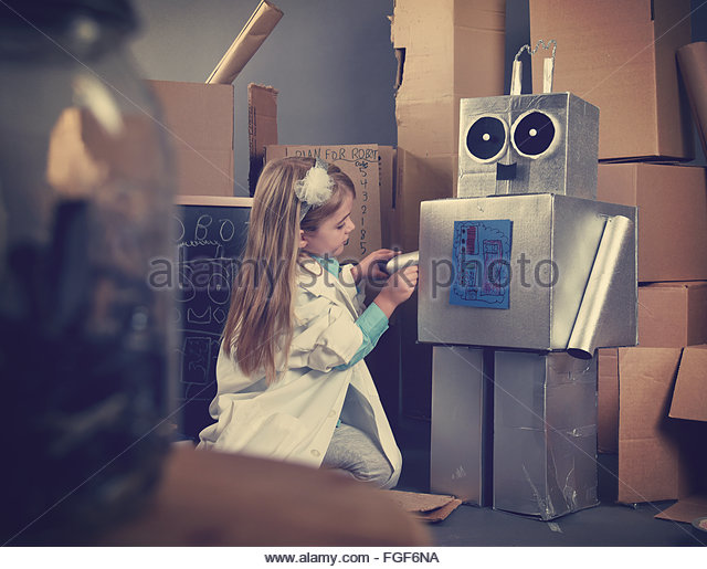 A science student is inventing a metal robot out of cardboard boxes with tools. Use it for an education or imagination - Stock Image