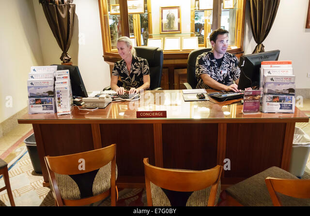 Hawaii Hawaiian Honolulu Waikiki Beach resort Hilton Waikiki Beach hotel lobby concierge desk help man woman service - Stock Image