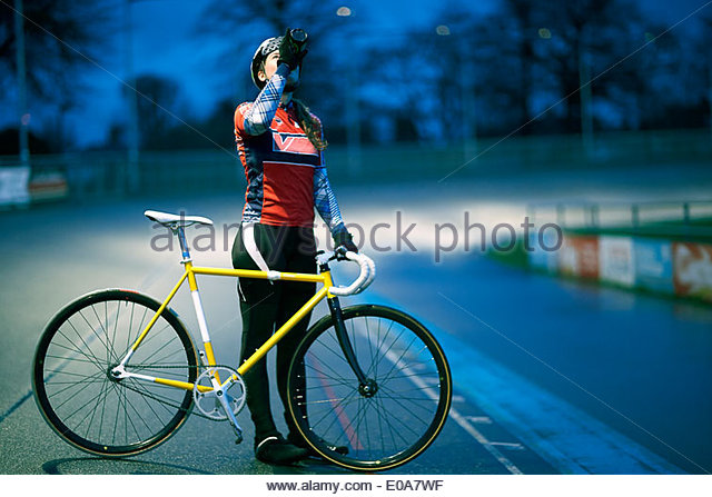 Young female cyclist drinking from water bottle at velodrome track - Stock Image