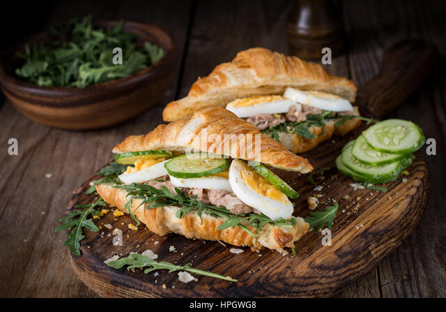 Tuna croissant sandwiches on wooden cutting board. Fresh tasty tuna salad sandwiches. - Stock Image