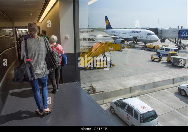Passengers taking the walkway to their awaiting airplane. - Stock Image