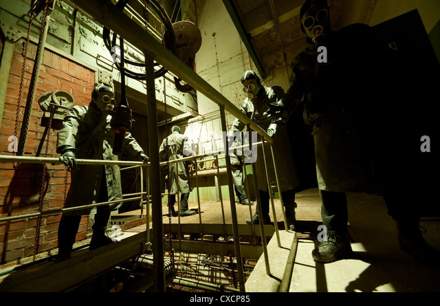 Gas masked menacing men posing in industrial setting - Stock Image