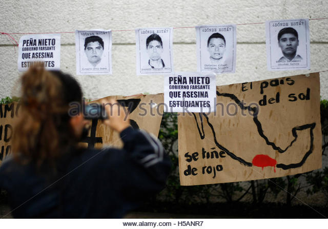 A demonstrator takes photographs of posters of missing students of the Ayotzinapa Teacher Training College 'Raul - Stock Image
