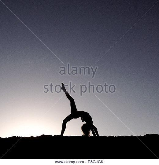 Woman doing yoga at beach at down - Stock-Bilder