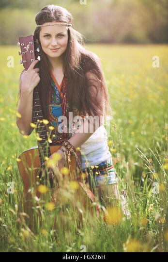 Beautiful hippie woman posing with guitar . Nature harmony - Stock-Bilder