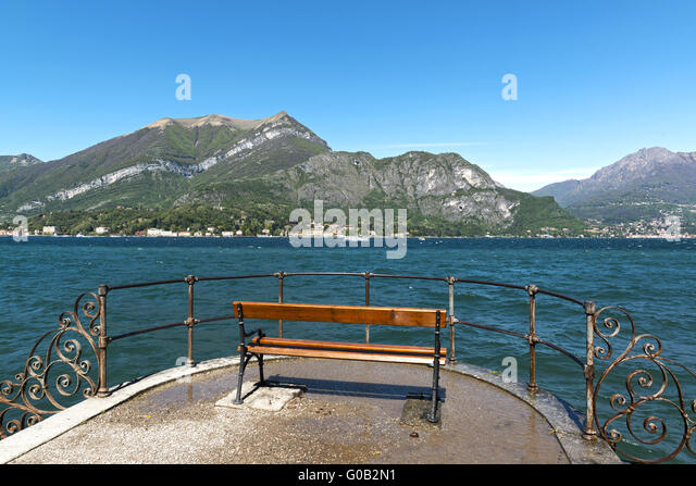 bench with beautiful views of Lake Como in a quiet and sunny spring morning, Bellagio - Stock Image