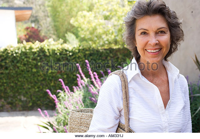 Woman outside home with large purse smiling - Stock Image