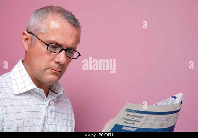 Businessman reading the latest share prices in a financial newspaper - Stock Image
