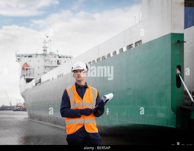 Port Worker In Front Of Container Ship - Stock Image