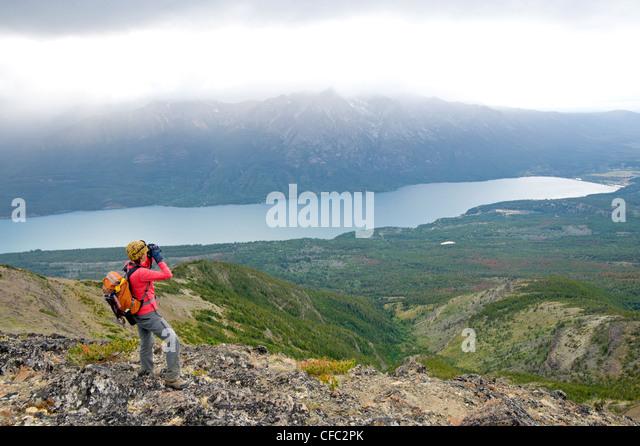 A woman surveys over Tatlayoko Lake with binoculars, British Columbia Coast Mountains - Stock Image