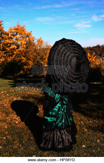 Rear view of Victorian woman holding an umbrella - Stock Image