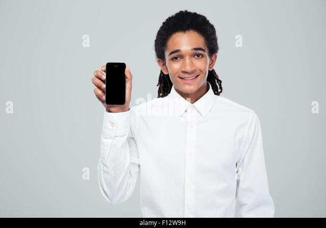 Portrait of a smiling afro american businessman showing blank smartphone screen over gray background - Stock Image