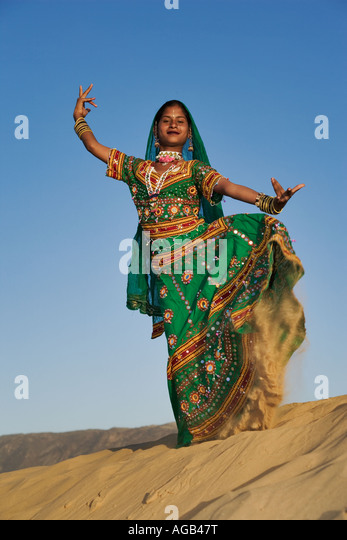 Young Indian women in a beautifully decorated saris performing a traditional Rajasthani dance Thar desert outside - Stock Image