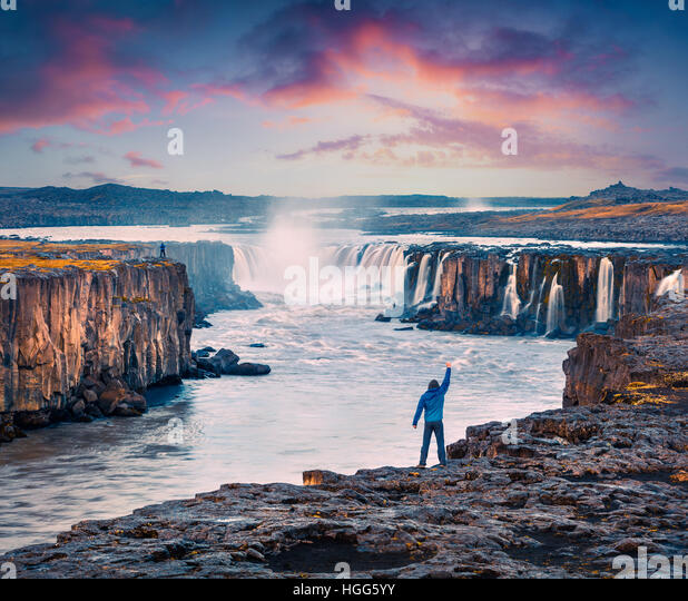 Tourist standing on the standing on the edge of Jokulsa a Fjollum river with raised hand and enjoying sunrise. Colorful - Stock Image