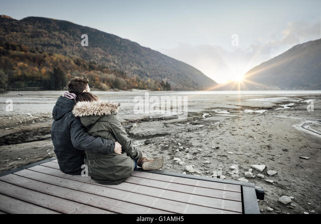Loving couple sitting on a pier, hugging and looking away, love and feelings concept - Stock-Bilder