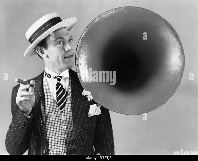 Man holding a cigar and standing near a victrola horn - Stock Image