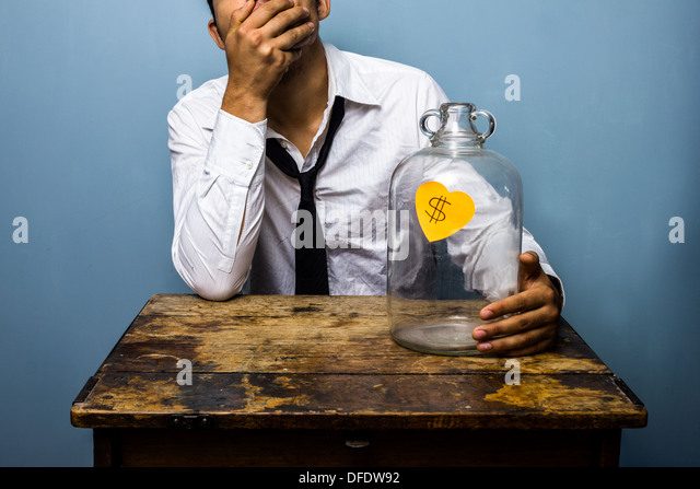Sad young businessman has spent all the money in his piggy bank - Stock Image