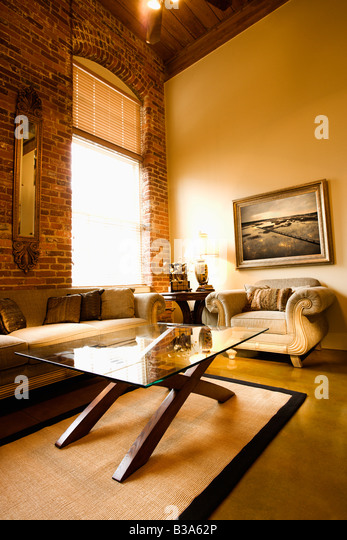 Interior of living room with large window brick wall coffee table and sofa - Stock Image