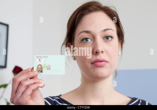 Woman holding identification card - Stock Image