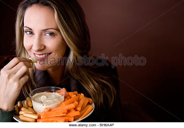A mid adult woman eating crudites and dips - Stock Image