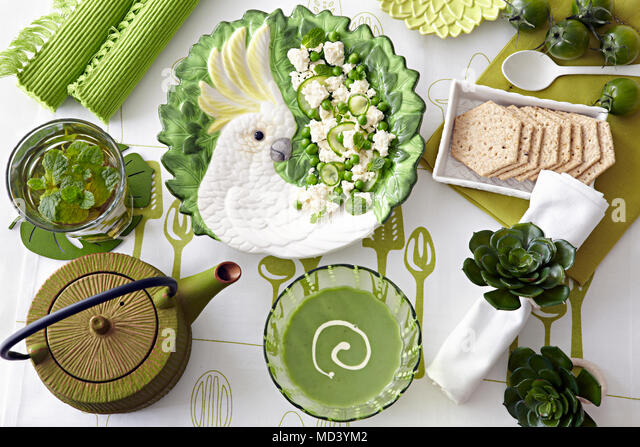 Overhead view of table with green pea soup, fresh salad and water biscuits - Stock Image