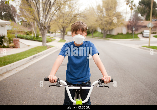 Boy on bicycle wearing dust mask - Stock Image