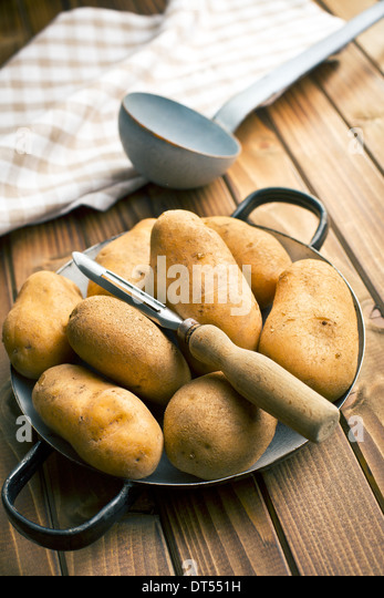 wooden peeler and potatoes on wooden table - Stock Image