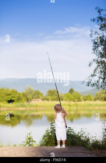 Cute little girl fishing on the lake with - Stock Image